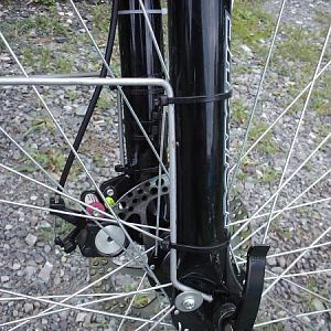 10 Guage round wire stock fender stays that are wire tied to the fork and held at the bottom with washers.